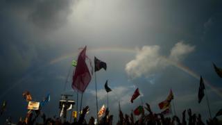 A rainbow is cast over Glastonbury revellers