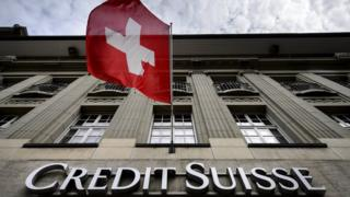 Sign on Credit Suisse building with Swiss flag