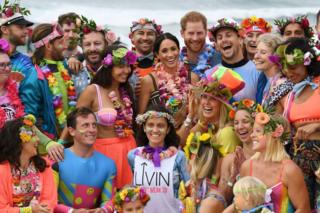 Prince Harry and Meghan, the Duchess of Sussex, pose with a local surfing community group at Bondi Beach in Sydney