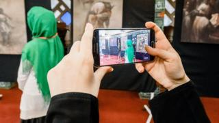 A woman takes pictures of another woman wearing a headscarf and looking at a picture cycle on display at the Blue Mosque in Hamburg, northern Germany, on October 3, 2016, which marks the Open-Mosque-Day.