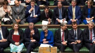 May aparece sentada em meio a dezenas de parlamentares enfileirados