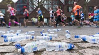 Runners run past water bottles as they take part in the 2016 London Marathon in London