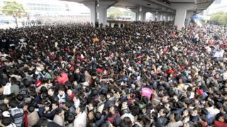Pasajeros tratando de entrar a la estación de tren de Cantón.