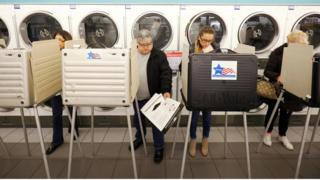 Several people are shown standing in voting booths in a Laundromat