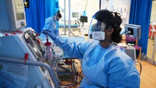 Clinical staff wear Personal Protective Equipment (PPE) as they care for a patient at the Royal Papworth Hospital in Cambridge.