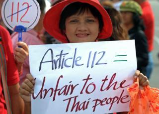 ผู้หญิงถือแผ่นป้ายต่อต้านการใช้ม.112