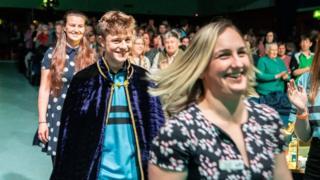 Twm Ebbsworth o Glwb Llanwenog, Ceredigion, enillydd y Gadair, yn cael ei dywys i'r llwyfan ar gyfer y seremoni