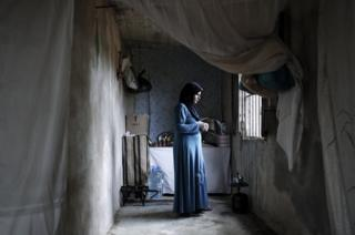 Nawal Gharab, 28, a mother of three, prepares tea in a one room house that has no running water or electricity, in Abreen, near Batroun, Lebanon, on October 5, 2013