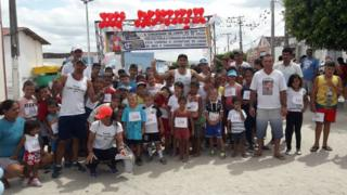 Ivanildo (ao centro) com as crianças que participaram de uma de suas corridas