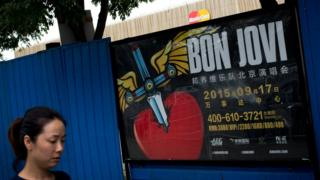 A woman walks past a billboard advertising the cancelled Bon Jovi concert in Beijing, on 9 September