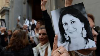 Campaigners holding up photos of Daphne Caruana Galizia