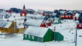 A town in typical Greenland style is pictured - brightly-painted wooden walls and triangular roofs covered in snow are the main features of these sparsely dotted homes