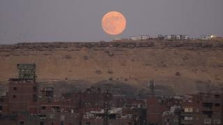 A picture sent by Emad Karim in Cairo, Egypt shows a glowing orange moon above reddish Egyptian sands