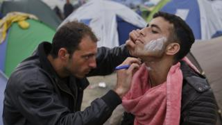 A barber shaves a migrant at the Idomeni camp (07 March 2016)