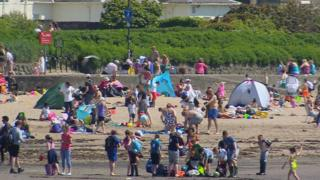 People enjoying the sun on south beach in Troon