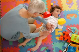 Childminder changes nappy