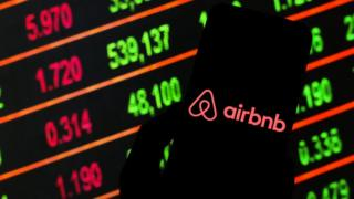 Airbnb logo on a smartphone with stock market prices in the background.