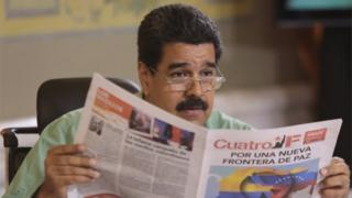 """Nicolas Maduro reads a pro-government newspaper as he speaks during his weekly broadcast """"In contact with Maduro"""" in Caracas on 15 September, 2015."""