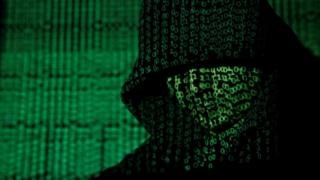 Projection of cyber code onto a hooded man