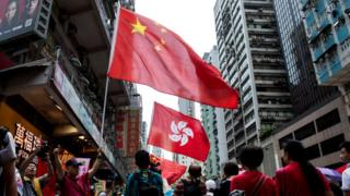 People hold the Chinese and Hong Kong flags as they take part in a pro-government rally in Hong Kong on August 17, 2014.