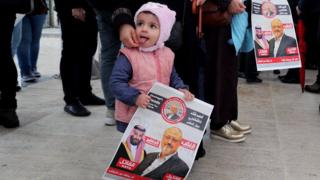 A child holds photos of slain Saudi journalist Jamal Khashoggi as people gather to perform an absentee funeral prayer at Fatih Mosque in Istanbul, Turkey, 16 November 2018
