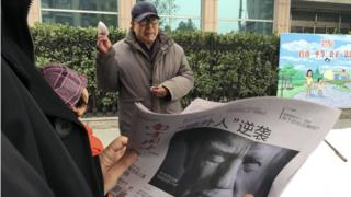 Man in Beijing reads paper featuring picture of Donald Trump