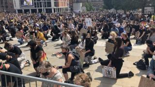 Protesters on the ground bent on one knee