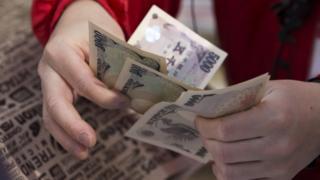 An employee counts Japanese yen notes