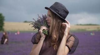 Devojka pozira za fotografiju na polju lavande