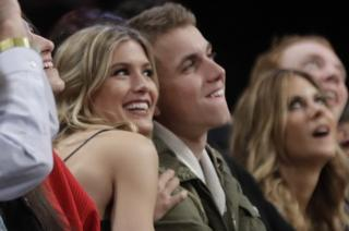 Eugenie Bouchard, left, poses for photographs with her blind date, John Goehrke, right, during the second half of an NBA basketball game