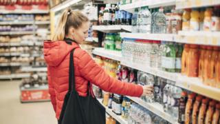 A woman selects a single-use drink from a supermarket shelf