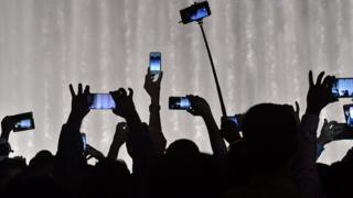 People holding up mobile phones