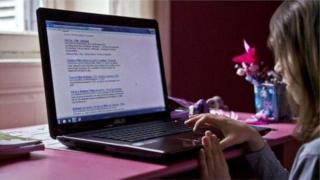 Bé gái ngồi dùng máy tính xách tay