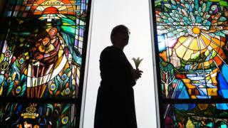 The stained glass memorial window the a woman standing holding a lily