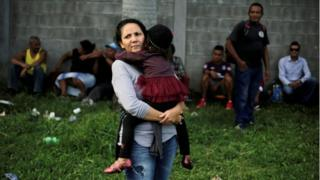 A Honduran woman carries her daughter as they wait to leave with a new caravan of migrants in San Pedro Sula