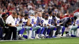 Jugadores de los Vaqueros de Dallas se arrodillan durante el himno de EE.UU.