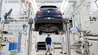 VW employees work on an electric car e-Golf