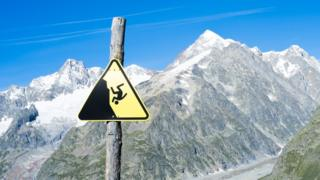 Slippage danger sign with Miage Glacier and Combal peaks in the background, August 2014