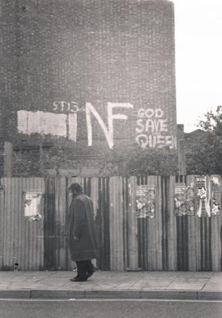A man walks alongside a building daubed with National Front graffiti