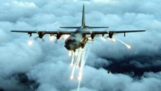File photo of an AC-130 gunship firing flares in several directions mid-flight