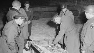 Generais examinam uma mala de talheres de prata, parte do saque alemão armazenado em uma mina de sal em Merkers.