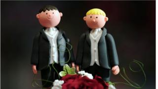 A wedding cake topper featuring two men