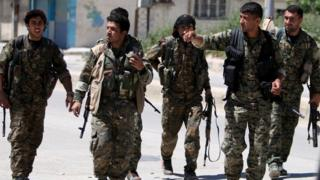 Kurdish fighters from the People's Protection Units (YPG) walk along a street in the southeast of Qamishli city, Syria (22 April 2016)