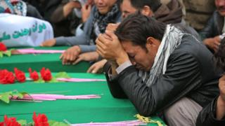 Afghan men mourn the seven victims whose throats were cut by unidentified militants over the weekend