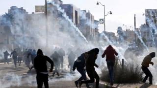 Palestinian protesters run from tear gas near the Jewish settlement of Beit El, near Ramallah