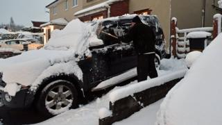 A motorist clears the snow from a 4x4 vehicle in Bristol