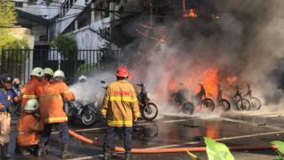 เจ้าหน้าที่ช่วยกันดับเพลิงหลังเกิดเหตุระเบิดที่โบสถ์แห่งหนึ่งในสุราบายา