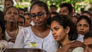 A woman cries as she holds her friend for comfort during a mass funeral at St Sebastian's Church on April 23, 2019 in Negombo, Sri Lanka