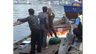 (캡션) 지난 15일 삼척항 부두에서 북한 선원 4명이 해양경찰에 조사받는 모습
