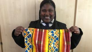 Image of Sainabu Nije holding a colourful Gambian skirt.